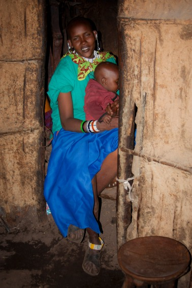 Massai mother and young boy sit in a pitch black hut in northern Tanzania.