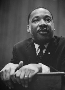 "alt=""Rev. Dr. Martin Luther King, Jr. leaning on a lectern"""