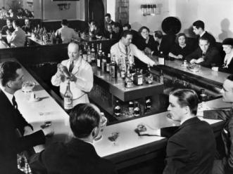 "alt=""Bartender prepares drinks for patrons at a popular Prohibition era speakeasy during """