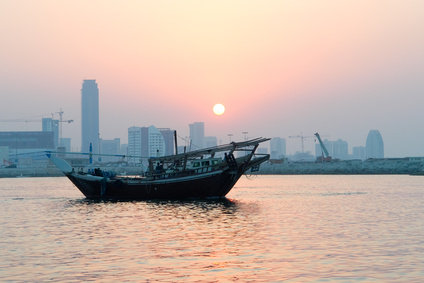 Bahrain city silhouette and fishing dhow at sunset.