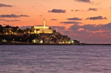 The Tel Aviv promenade at sunset.The lights of Jaffa at sunset