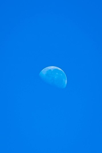 Earth's moon and a blue sky in the afternoon, Namibia