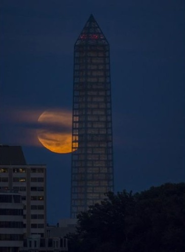 "The Washington Monument under restoration in 2013 with the ""Supermoon"" in the background (photo courtesy NASA)"
