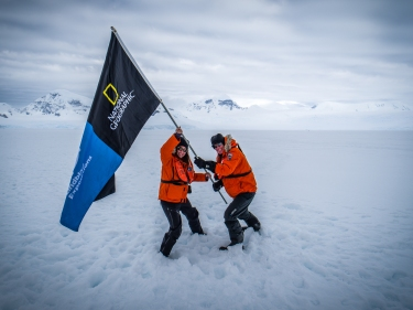 Hoisting a National Geographic / Lindblad Expeditions flag on the Antarctic continent with explorer Peter Hillary -- life can be surreal. (Credit: Jonathan Irish)