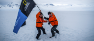 Hoisting a National Geographic / Lindblad Expeditions flag on the Antarctic continent with explorer Peter Hillary — life can be surreal. (Credit: Jonathan Irish)