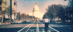 DC bike commuter rides toward the U.S. Capitol Building on Pennsylvania Avenue (Credit: Stefanie Payne)